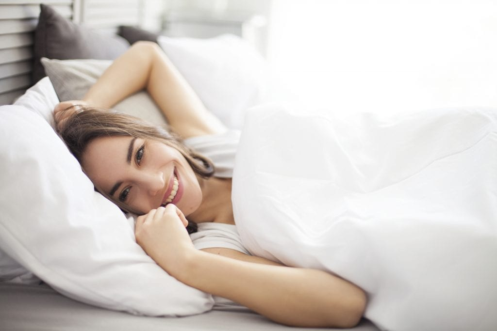 Beautiful woman in bed waking in the morning refreshed and happy.