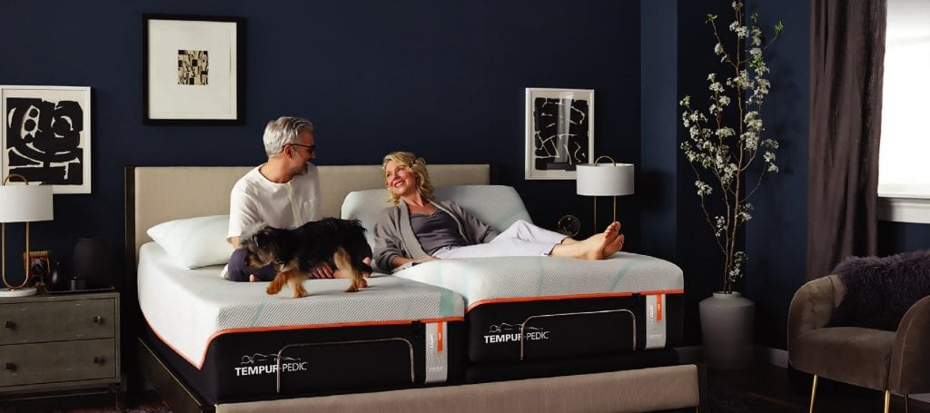 an older couple sitting on a Tempurpedic mattress with their puppy
