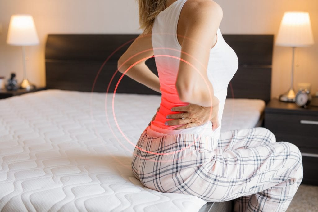 Female suffering from back pain because of uncomfortable mattress