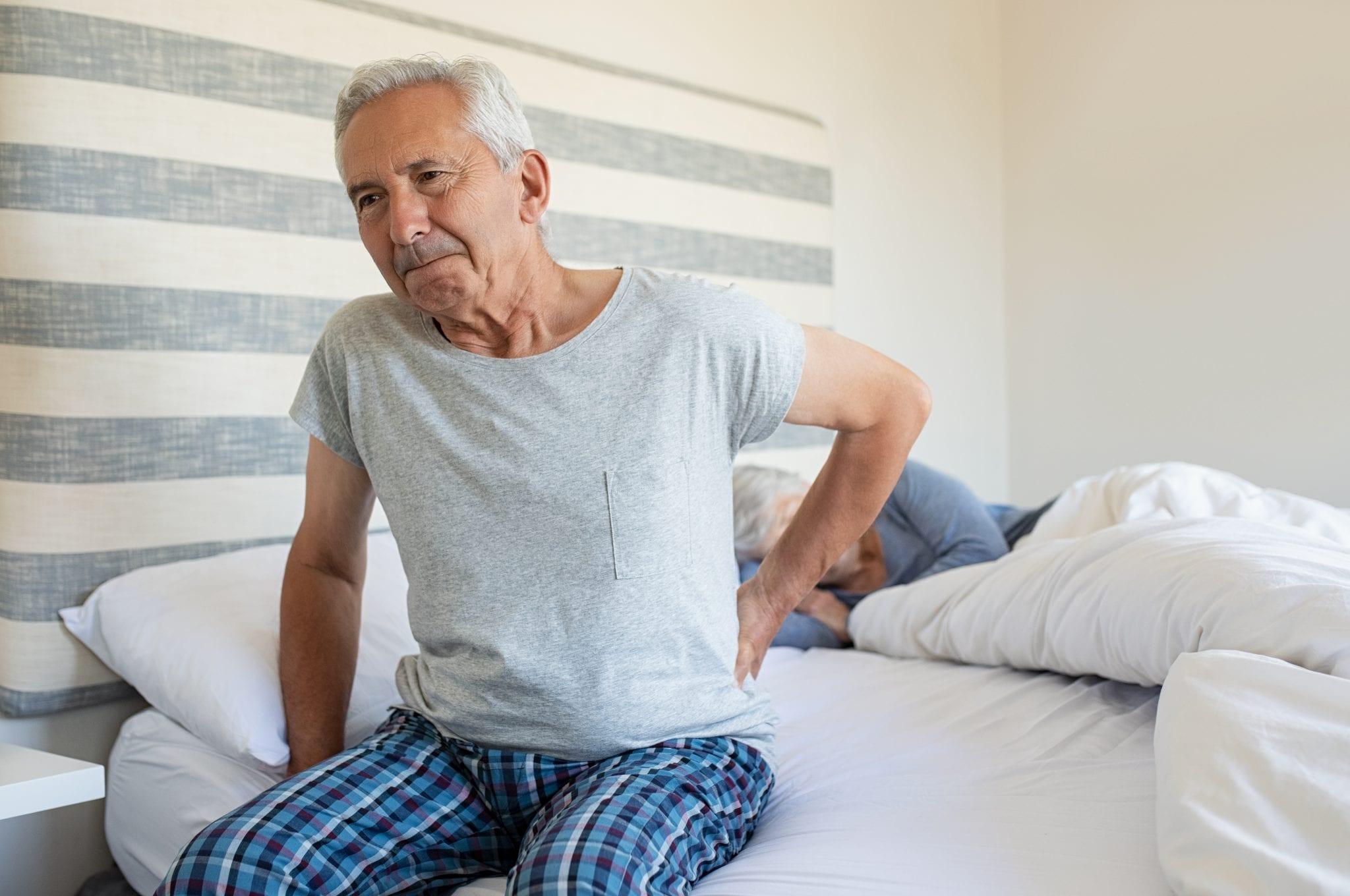 Elderly man suffering backpain from his bed.