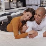 man and woman laying on mattress in mattress store