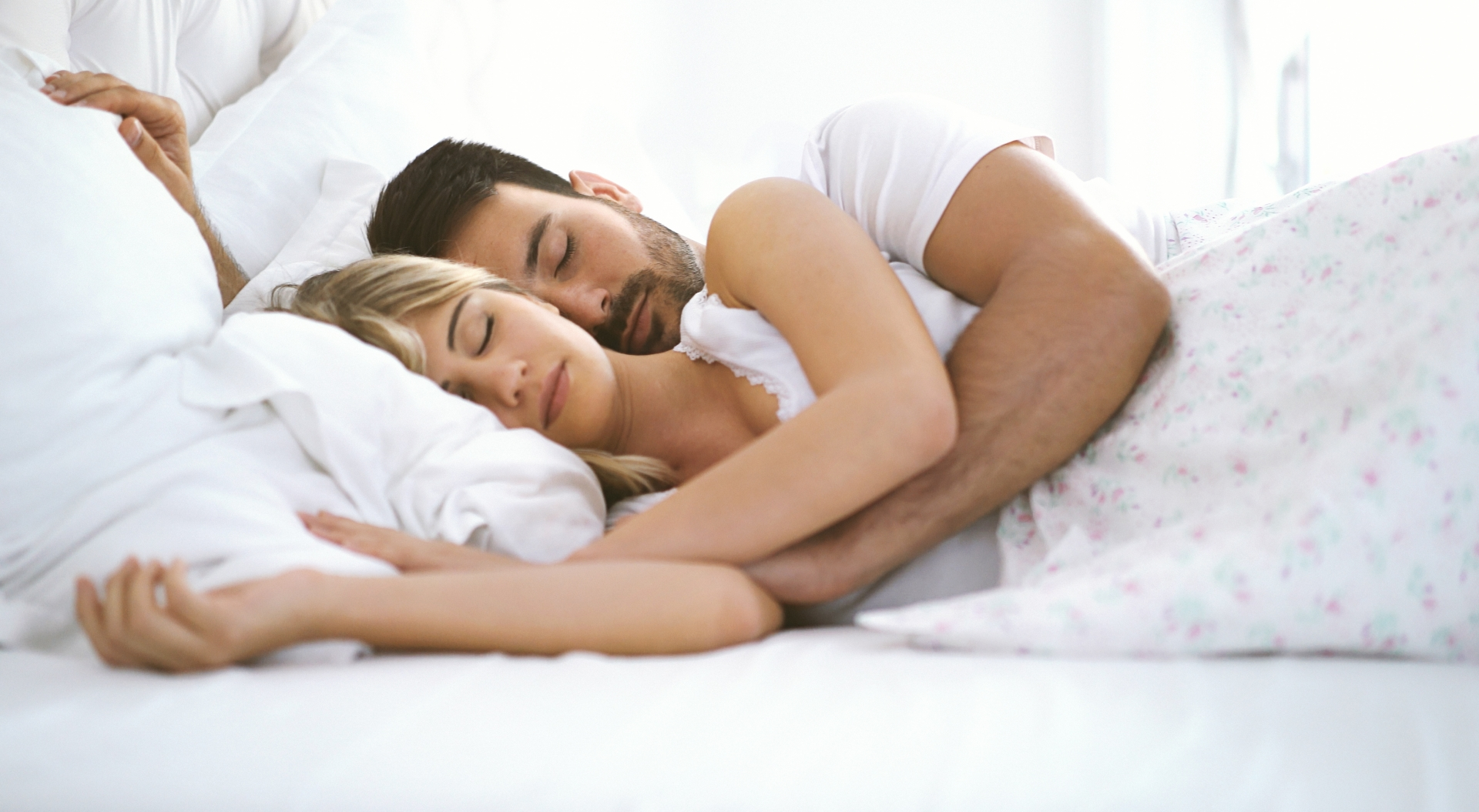 A couple side sleeping in bed