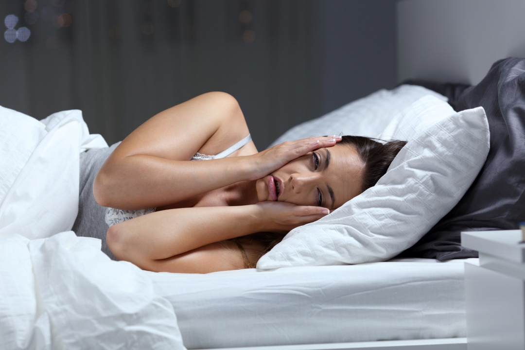 Woman laying in bed stressed that she can't sleep