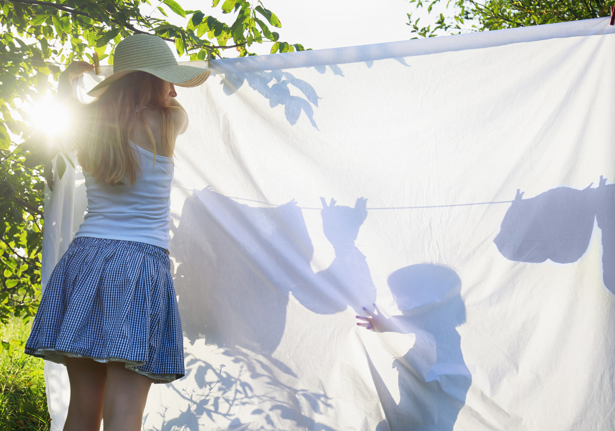 Mother hang drying bed sheets