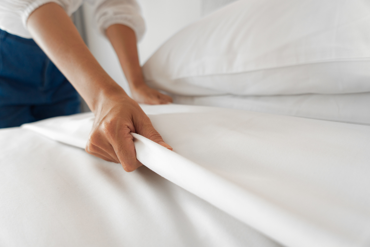 Women making up bed sheets on bed